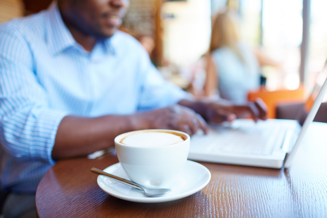 Male sitting in cafe with laptop and coffee